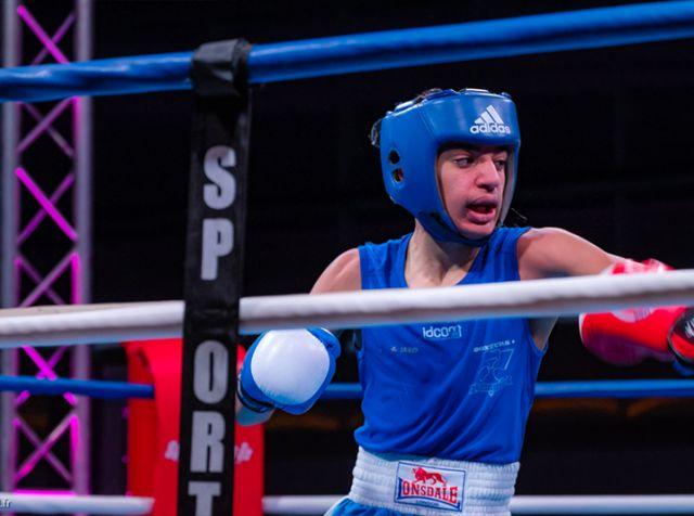 Jeune boxeur décochant un crochet du gauche à son adversaire lors d'un combat de boxe